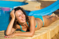 Girl sunbathing at poolside Royalty Free Stock Image