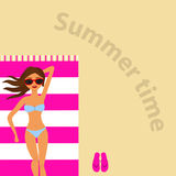 A girl is sunbathing on a towel on the beach Royalty Free Stock Photo