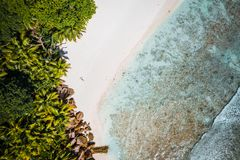 Girl sunbathing on tropical cocos beach with beautiful rocks, palm trees and ocean waves. Aerial drone shot. Seychelles royalty free stock images