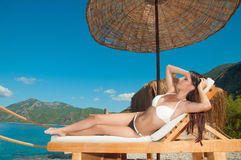 Girl sunbathing in VIP bungalow overlooking the sea Stock Images