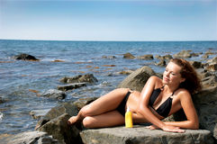Girl of sunburn on stones Stock Images