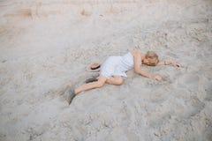 Girl sundress lies sand sad crying longing. Girl in a sundress lies on the sand sad crying longing loneliness conceptual stock photography