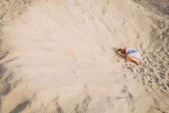 Girl sundress lies sand sad crying longing. Girl in a sundress lies on the sand sad crying longing loneliness conceptual stock image