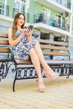 Girl in a sundress sits on a bench stock photo