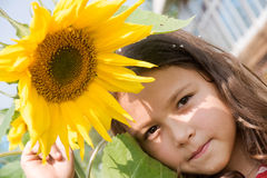 Girl with sunflower. Portrait of the smiling girl with with sunflower in garden Stock Photos