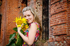 Girl with a sunflower. Blonde girl standing with a sunflower against a brick wall Stock Photo