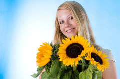 The girl with a sunflower. The attractive blonde in studio holds a sunflower in hands Royalty Free Stock Photos