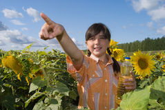 The girl with sunflower and bottle of oil Royalty Free Stock Image