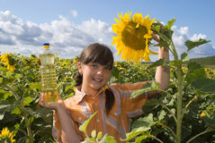 The girl with sunflower and bottle of oil Stock Photo