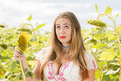 Girl on a sunflower field. Young cute girl posing in sunflower field Royalty Free Stock Photo