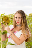Girl on a sunflower field. Young cute girl posing in sunflower field Stock Photo