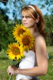 Girl with sunflowers. Girl in naturul background holding flowers Stock Photography