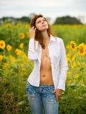 The girl and sunflowers. The girl in a white shirt and jeans costs in sunflowers Royalty Free Stock Images