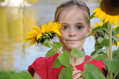 Girl with sunflowers. Cute schoolgirl portrait  with sunflowers outside in the garden Stock Image