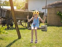 The girl with the sunflowers on her head is swinging on a vintage swing in the village in summer day. Beautiful girl in the rays of the sun with the decoration Royalty Free Stock Photo