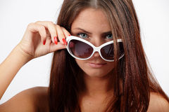 Girl with a sunglasses. Girl looking through white sunglasses Royalty Free Stock Photos