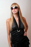 Girl in sunglasses. Girl in a black dress and sunglasses Stock Photo