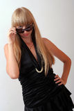 Girl in sunglasses. Girl in a black dress and sunglasses Royalty Free Stock Images