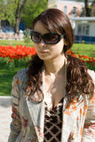 Girl in Sunglasses. Darkhaired young woman or girl in bright sunshine, wearing sunglasses, garden in background Stock Photo