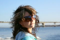 Girl with sunglasses. Attractive girl with sunglasses, wide river and bridge in foreground Royalty Free Stock Images