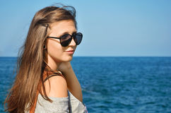 Girl with sunglasses. Pretty young girl with sunglasses on at the beach Stock Image
