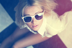 The girl in sunglasses. Sits on a floor in a cage Royalty Free Stock Photo