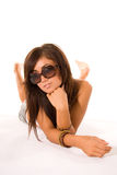 Girl with sunglasses. A studio view of a pretty teenage model casually lying on a white floor, wearing sunglasses Royalty Free Stock Photo