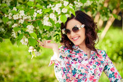 Girl in sunglasses in a blossoming apple-tree royalty free stock images