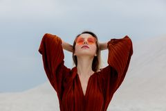 Girl in a sunglasses and burgundy color blouse on a white sand. Beach location stock images