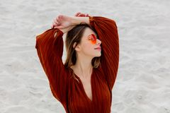 Girl in a sunglasses and burgundy color blouse on a white sand. Beach location royalty free stock photography