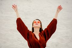 Girl in a sunglasses and burgundy color blouse on a white sand royalty free stock photo