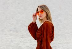 Girl in a sunglasses and burgundy color blouse on a white sand stock photos