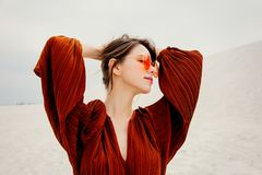 Girl in a sunglasses and burgundy color blouse on a white sand. Beach location royalty free stock image