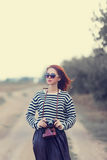 Girl in sunglasses and camera Royalty Free Stock Image
