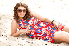 Girl in sunglasses and dress lying on beach Royalty Free Stock Photo