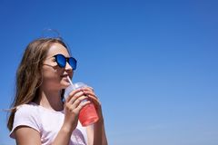 Girl in sunglasses drinking cold lemonade. Through a straw in summer sunny day, over blue sky stock photo