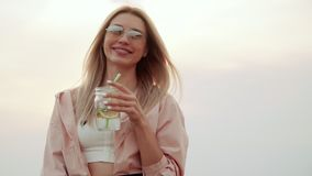 Girl with sunglasses drinks summer urban cocktail and smiles