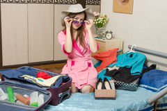 The girl in sunglasses and a hat packs a suitcase on vacation Stock Images