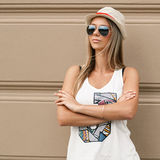 Girl in sunglasses and a hat stands near the wall. Travel Stock Photos