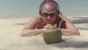 Girl in sunglasses and headphones, lying on the sand near the sea and looks at the coconut. stock footage