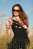 Girl in sunglasses holding beads Stock Photo