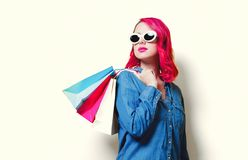 Girl in sunglasses holding a colored shopping bags. Young pink hair girl in sunglasses and blue shirt holding a colored shopping bags royalty free stock photos