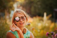 Girl in sunglasses is holding a flower in front of her face, closing one eye. The concept of Russian beauty, a gentle blonde with. A girl in sunglasses is Royalty Free Stock Images