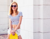 Girl in sunglasses holding skateboard Royalty Free Stock Photography