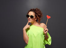 Girl in sunglasses holding small red heart Stock Images