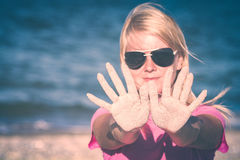 Girl in sunglasses. Instagram stylisation. Girl in sunglasses show hands covered with sand on a blue sea background. Instagram stylisation Royalty Free Stock Photos