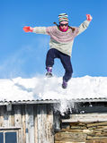 Girl jumping in snow. Girl with sunglasses jumping from a roof, with blue sky in the background Royalty Free Stock Image