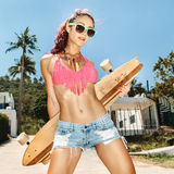 Girl in sunglasses with longboard Royalty Free Stock Image
