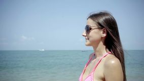 Girl in sunglasses looks and admires the sea. close-up. 4K. stock video