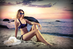 Girl with sunglasses lying on a beach in sunset Stock Image